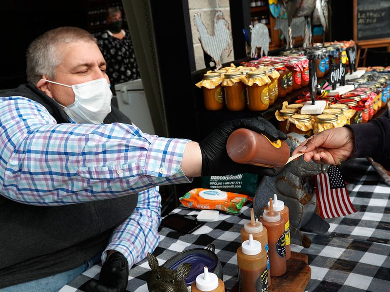 A masked Carey File of Delta Ridge Sauces and Seasonings applies a single drop on a wooden taste spoon as he shows off his product line at the Mississippi Farmers Market in Jackson during the coronavirus outbreak.