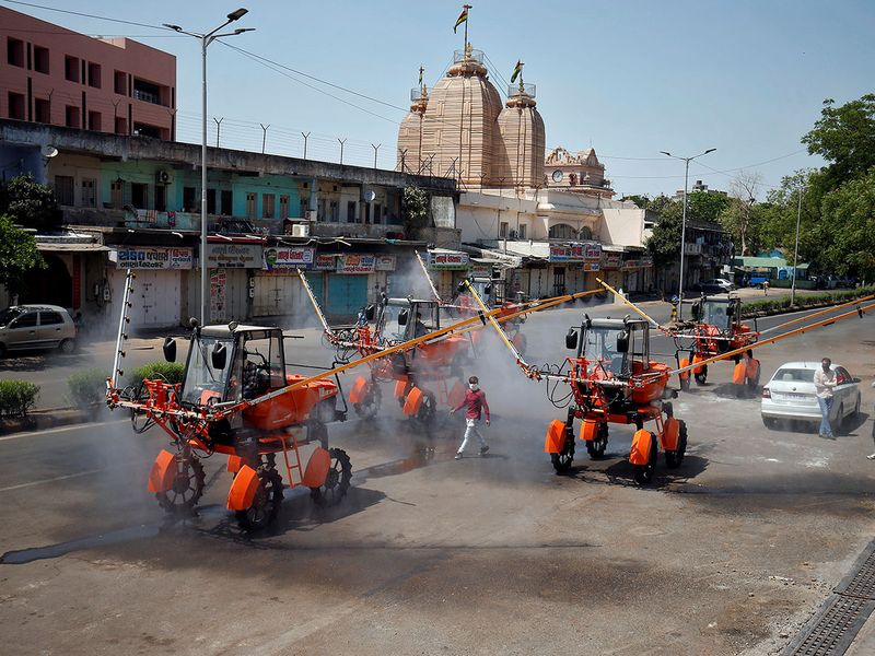 Members of Fire and Emergency Services decontaminate a road using boom sprayers to slow the spreading of coronavirus disease in Ahmedabad.