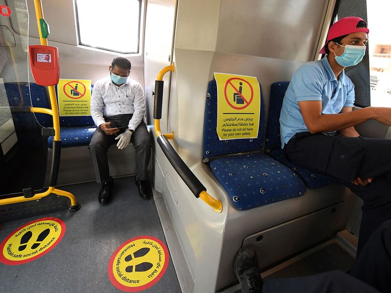 Workers use a bus in Dubai with sings plastered inside to help passengers implement the rules of social distancing, amid strict measures imposed by the authorities in a bid to slow down the spread of the novel coronavirus in the Emirates.