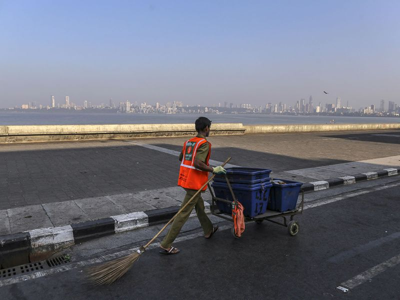 A cleaner walks in the Marine Drive area during a lockdown imposed due to the coronavirus in Mumbai, India.