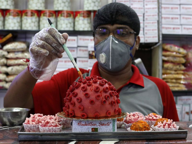 A confectioner applies finishing touches to a replica of coronavirus made out of sweets at a confectionary workshop in Kolkata.
