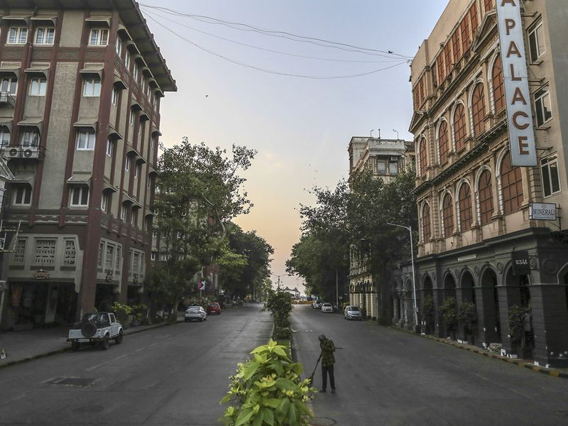 A man cleans up a street in the Colaba area during a lockdown imposed due to the coronavirus in Mumbai.
