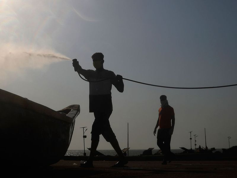 A man sprays disinfectant on a fishing boat during a countrywide lockdown in Mumbai.