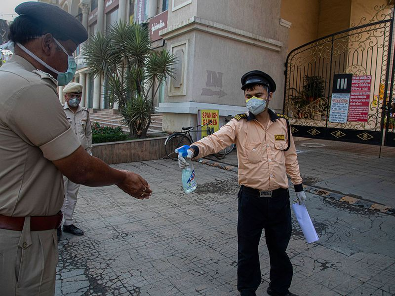 A security guard sanitizes the hands of a police officer after a person from their apartment complex was found to be COVID-19 positive, in Gauhati.