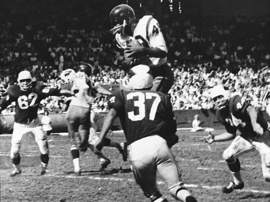 Bobby Mitchell of the Washington Redskins jumps to haul in a pass from quarterback Norman Snead during an NFL game against the St. Louis Cardinals in 1962