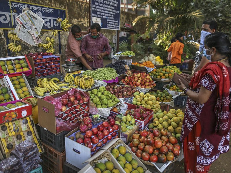 Customers wearing protective face masks shop for fruit at a market during a lockdown imposed due to the coronavirus in Mumbai.