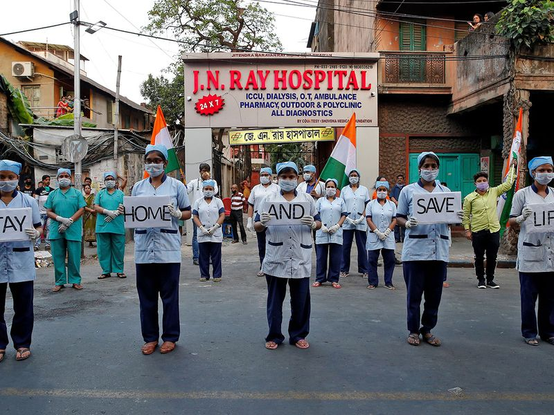 Medical staff members hold placards as they stand outside a hospital to show solidarity with people who are affected by COVID-19 and with doctors, nurses and other healthcare workers from all over the world in Kolkata.
