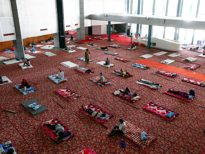 Migrant workers and homeless people rest inside a sports complex turned into a shelter in New Delhi.
