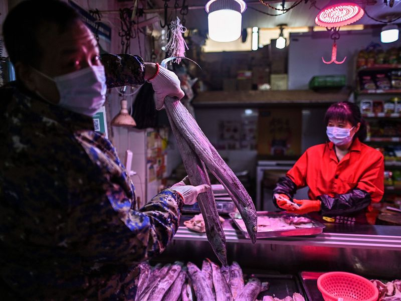 A man wearing a face mask holds a fish in a market in Wuhan, in China's central Hubei province.  Wuhan, the central Chinese city where the coronavirus first emerged last year, partly reopened on March 28 after more than two months of near total isolation for its population of 11 million.