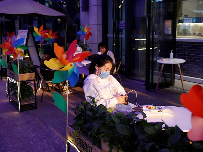 A woman wearing a face mask sits outside a restaurant at a shopping complex in Beijing.