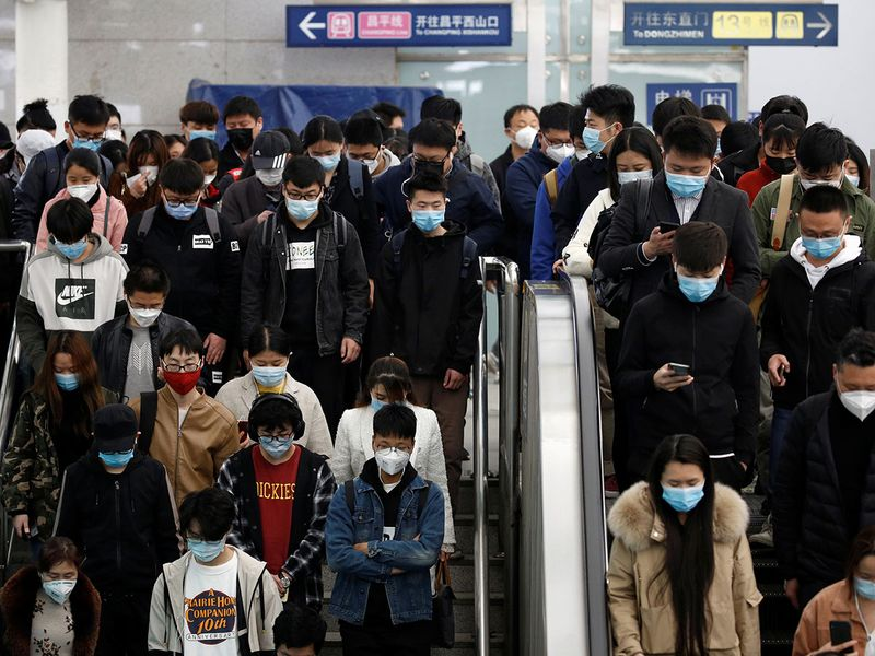People wearing face masks stand on an elevator inside a subway station during morning rush hour in Beijing, China.