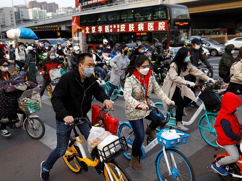 People wearing protective face masks ride bicycles on a street in Beijing, China.