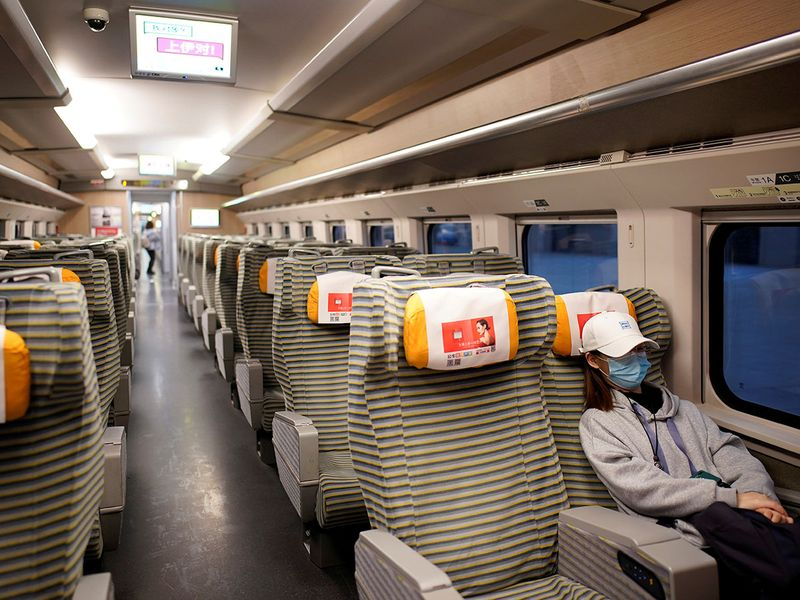 A passenger sits inside a high-speed train at Hankou Railway Station after travel restrictions to leave Wuhan, the capital of Hubei province and China's epicentre of COVID-19 outbreak, were lifted.