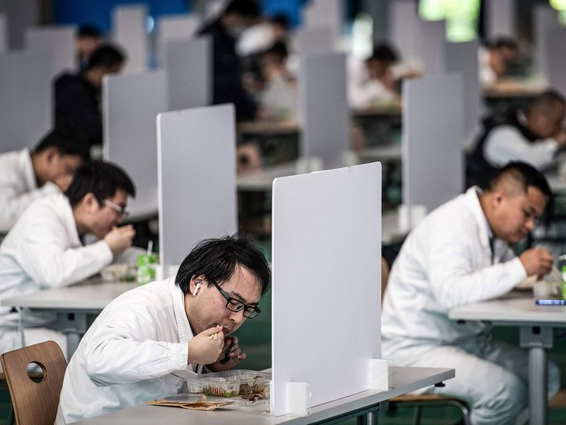 Employees eating during a lunch break at an auto plant of Dongfeng Honda in Wuhan in China's central Hubei province. Thousands of relieved citizens streamed out of China's Wuhan on April 8 after authorities lifted months of lockdown at the coronavirus epicntre, offering some hope to the world despite record deaths in Europe and the United States.
