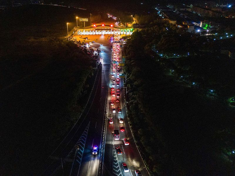 This aerial photo taken early on April 8, 2020 shows cars queueing at a highway toll station in Wuhan in China's central Hubei province, as they prepare to leave the city after authorities lifted a more than two-month ban on outbound travel.