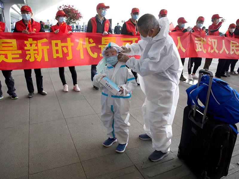 Travelers wearing face masks and suits to protect against the spread of new coronavirus walk past people holding a celebratory banner at Wuhan Tianhe International Airport in Wuhan in central China's Hubei Province.