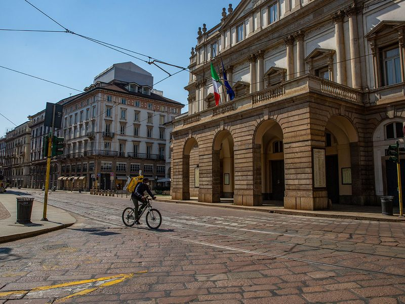 A cycle courier for Glovo, operated by Glovoapp 23 SL, passes the Teatro della Scala opera house in Milan, Italy.