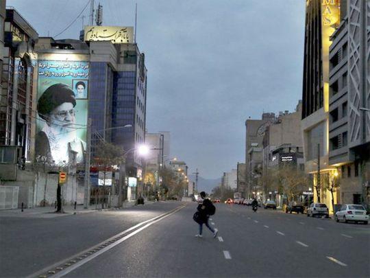 A pedestrian crosses an empty street in Tehran.