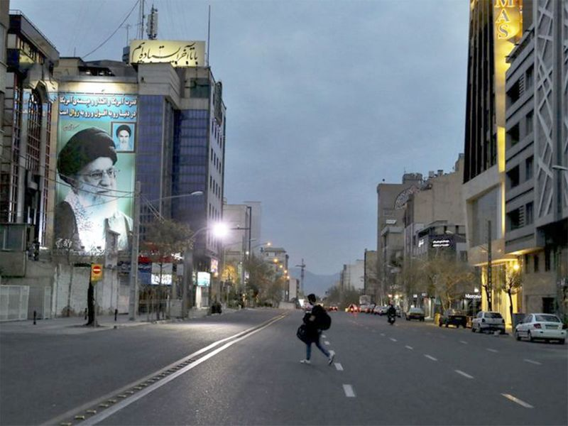 A pedestrian crosses an empty street in Tehran.
