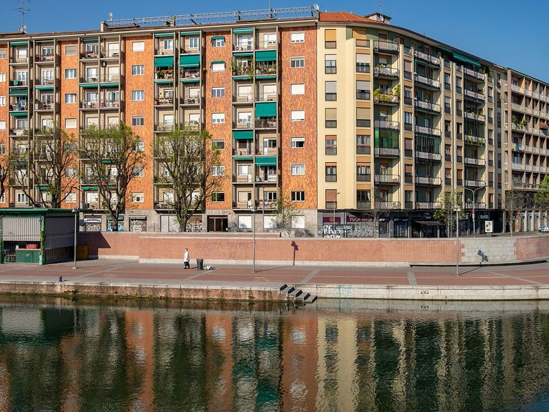 A pedestrian walks on the bank of the Darsena waterway in Milan, Italy.