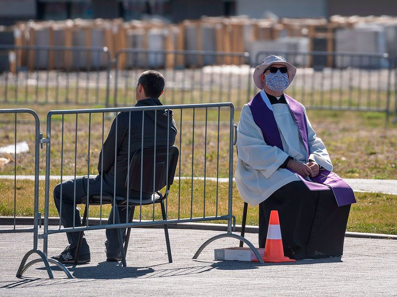 A priest wearing a face mask gives a confession to a believer in a parking lot in front of the Warsaw Temple of Divine Providence, in preparation towards the upcoming Easter, in Warsaw, Poland amidst the new COVID-19 pandemic.