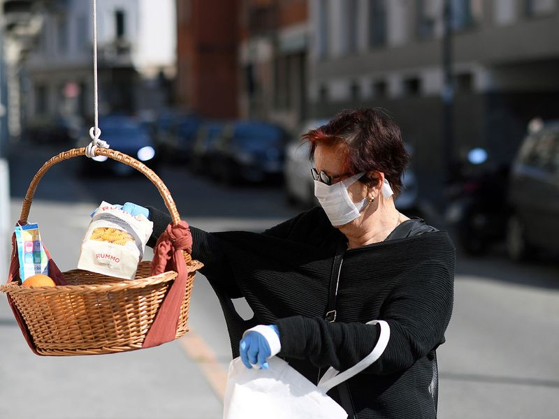 A woman puts groceries into a basket where people can donate or take free food, amid the COVID-19 outbreak in Milan, Italy.