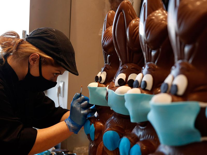 An employee of cake shop prepares chocolate Easter bunnies with masks in Lykovrisi, northern Athens.