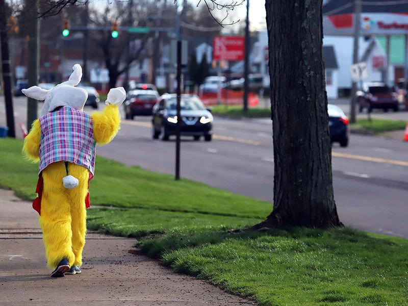 Maureen Salley, waves to motorists as she walks along Wyoming Avenue in Forty Fort, Pa.,