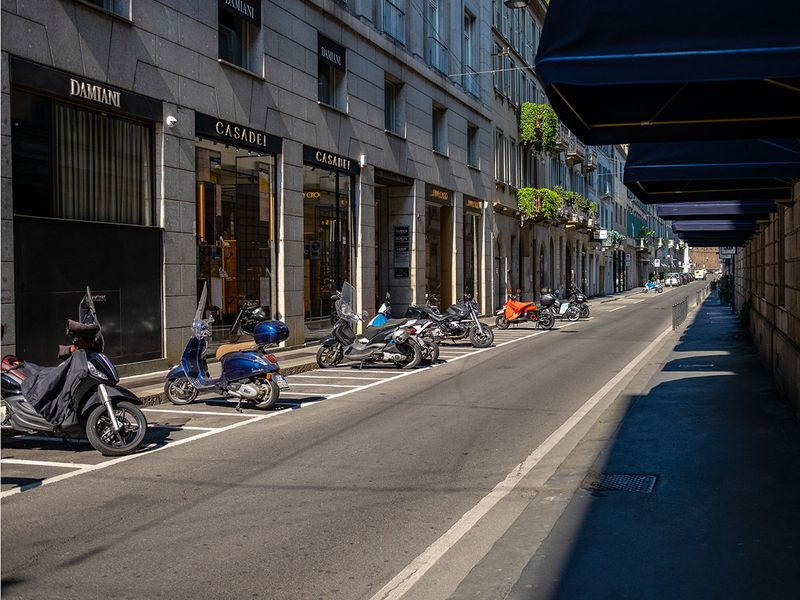 Mopeds sit parked outside closed luxury boutiques on Via Monte Napoleone, the fashion district artery in Milan, Italy.