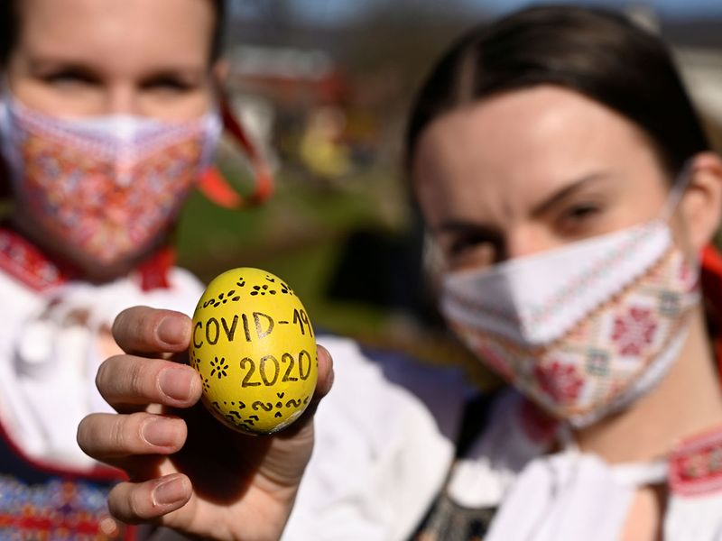 Vanda Mrazikova and Martina Kacenova, dressed in traditional costume with protective face masks, show a colored Easter eggs which reads COVID-19 and the year 2020, amid the COVID-19 outbreak, in the village of Soblahov, Slovakia.