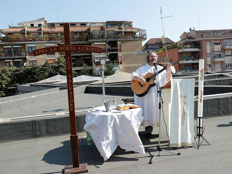 A priest leads an Easter Sunday Mass as he plays guitar on the roof of the Santissima Trinita a Villa Chigi parish church during the (COVID-19) outbreak in Rome, Italy.