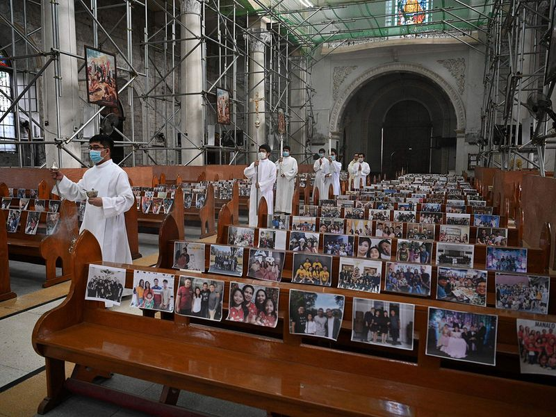 Catholic church altar boys walk down the aisle through the empty Holy Rosary parish church with photos of parishioners taped on church pews, as part of social distancing measures amidst the COVID-19 pandemic, at the start of a procession for Easter Sunday mass in Angeles City, Pampanga province.
