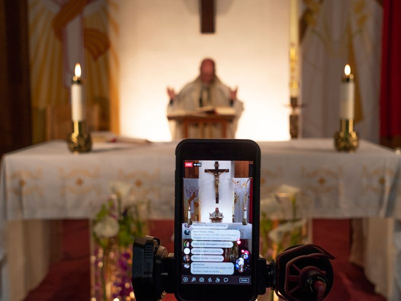 Pastor Nicolas Sanchez is seen on his iPhone used to live-stream in celebration of Easter Vigil Mass at St. Patrick Church in North Hollywood, California. The COVID-19 measures also have changed the way people worship, with churches and synagogues closed and many Passover and Easter services streamed online.