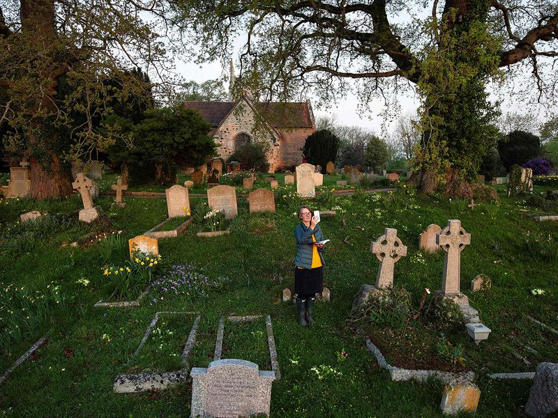 Priest-in-Charge Angie Smith, uses her smartphone to live-broadcast an Easter Sunday service to her congregation at dawn, from the churchyard of Old St. Mary's Church in Hartley Wintney, west of London.