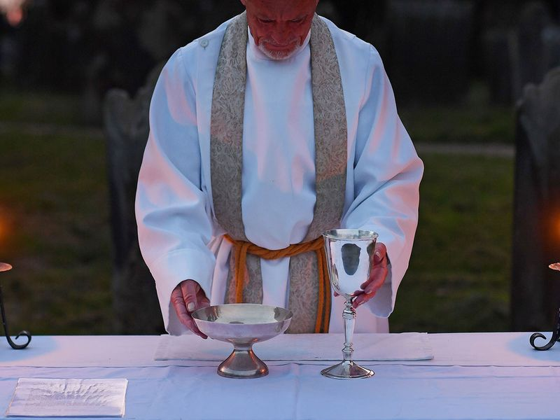 The Vicar of Brenchley Reverend Campbell Paget prepares the Lord's table ahead of an Easter Service, at dawn in the churchyard of All Saints' Church in Brenchley, south east England,  adhering to government advice on social distancing.  Easter events have been cancelled across the country, with the government urging the public to respect lockdown measures by celebrating the holiday in their homes, during the nationwide lockdown to combat the coronavirus pandemic.