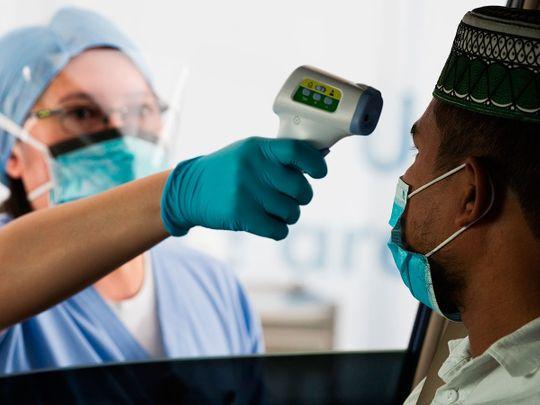 A staffer checks a man's temperature