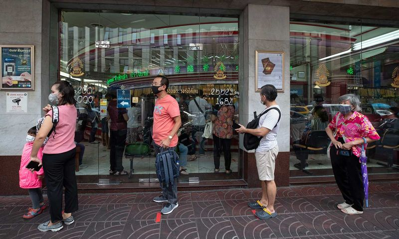 Customers practice social distancing to help curb the spread of the coronavirus wait to enter a  gold shop in Bangkok, Thailand, Tuesday, April 14, 2020. The new coronavirus causes mild or moderate symptoms for most people, but for some, especially older adults and people with existing health problems, it can cause more severe illness or death. (AP Photo/Sakchai Lalit)