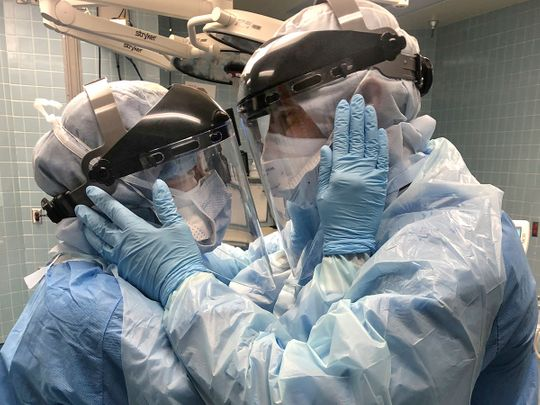 Nurses Mindy Brock and Ben Cayer, wearing protective equipment, hold each other and look into each other's eyes, in Tampa General Hospital in Tampa, Florida.