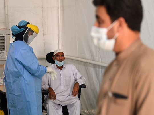 A health worker takes samples from expatriate workers