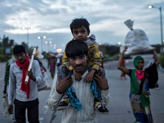 Indian migrant worker carries his son as they walk along a road with others to return to their village in New Delhi