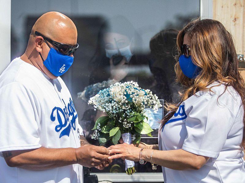 Philip Hernandez (L) puts the ring on his bride Marcela Peru, as Clerk Recorder Erika Patronas (C) looks on, during their wedding ceremony