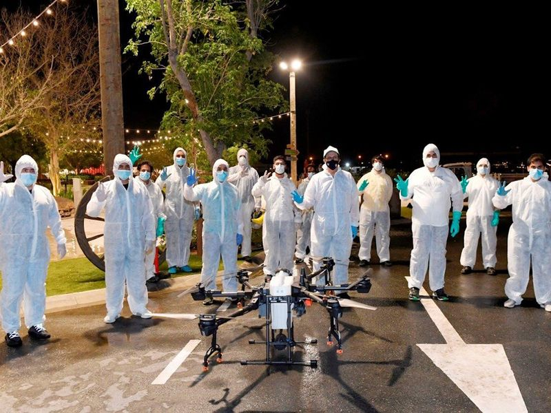 Sterilisation teams pose beside a drone in Al Khawaneej