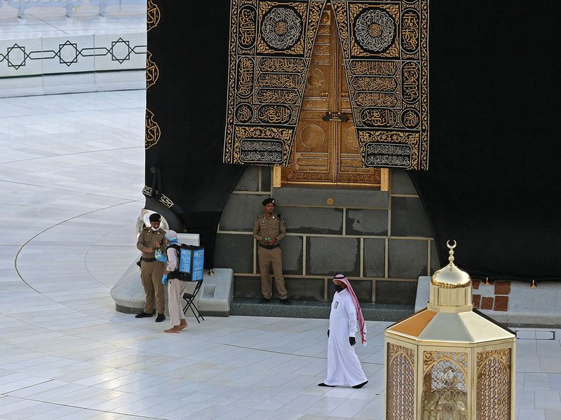 A picture shows Saudi policemen standing guard next to the Kaaba in Mecca's Grand Mosque, on the first day of the Islamic holy month of Ramadan.