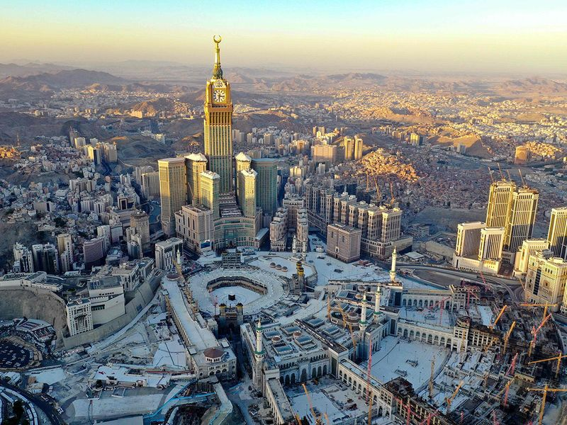 Above, an aerial view shows the Grand Mosque and the Mecca Tower in a deserted surrounding on the first day of the Muslim fasting month of Ramadan, in the Saudi holy city of Mecca.