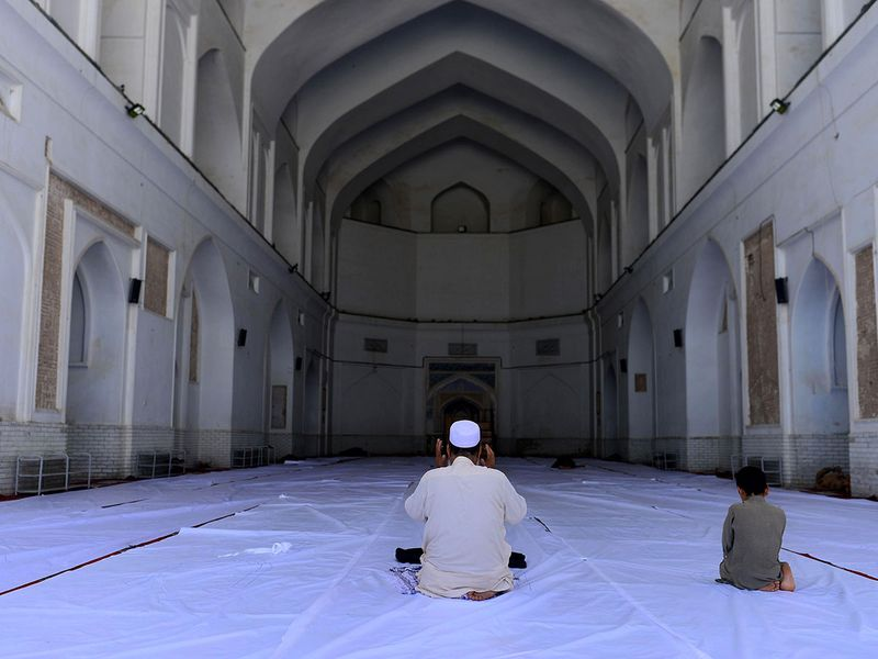 A Muslim man and a child offer prayers during the Islamic holy month of Ramadan at the Jami mosque, in Herat, Afghanistan.