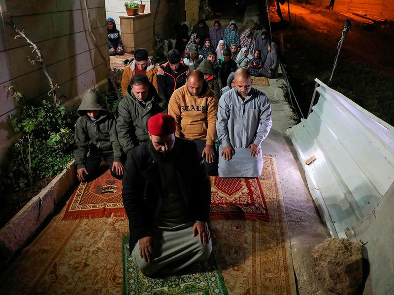 A Palestinian cleric pray with his family the night prayer known as Taraweeh outside their house during the holy month of Ramadan in the occupied West Bank city of Hebron as mosques are closed due to the COVID-19 pandemic.