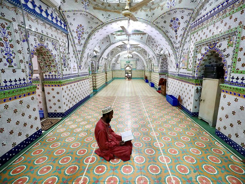 A devotee recites the Quran at the Star Mosque during Ramadan in Dhaka, Bangladesh.