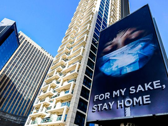 A view of an advertisement board on display in a street in Dubai, advising residents to remain at home.