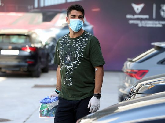 Luis Suarez walks wearing a protective face mask at the club's training ground in Barcelona
