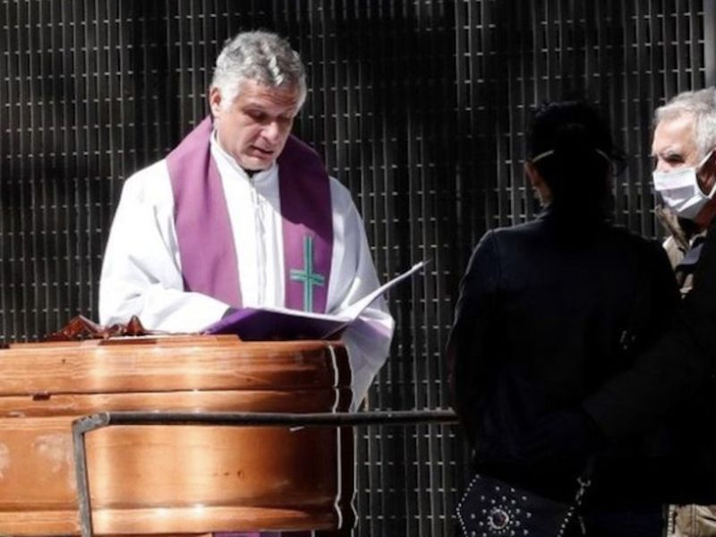 A priest conducts a funeral service in Pamplona, Spain, during the coronavirus pandemic.